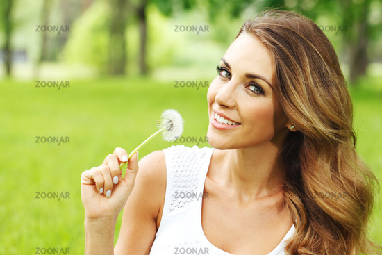 Woman in park with dandelion
