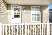 Porch of a house with beige vinyl wood siding and railing