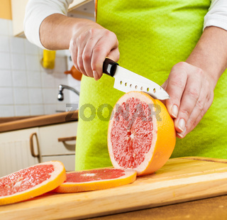 Woman's hands cutting grapefruit