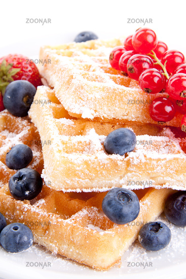 Fresh sweet waffles with icing sugar and berries on a plate isolated on white
