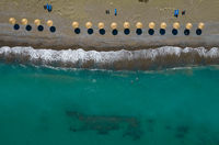 Aerial view from a flying drone of beach umbrellas in a row on an empty beach with braking waves.