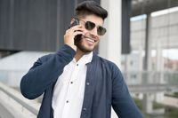 Handsome Man talking on cellphone at modern office building.