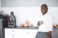 Successful Young Businessman. African American Guy Smiling In Kitchen With A Cup In Hand. Rich Investor In His Home Before Work. Concept Of Victory, Personal Growth