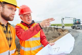 Bauleiter und Vorarbeiter mit Bauzeichnung auf Baustelle