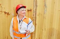 Frau als Architektin mit Bauplan und Checkliste