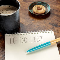To do list. A square shot of a blue pen on a paper notebook with coffee