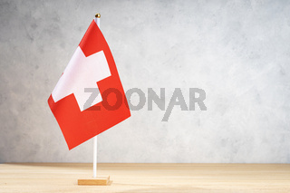 Switzerland table flag on white textured wall. Copy space for text, designs or drawings
