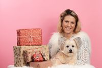 Mature woman with cute dog beside christmas presents