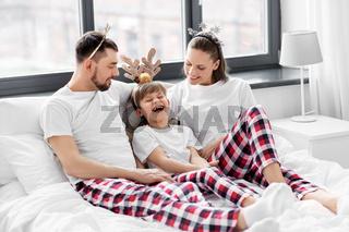 family in pajamas in bed in christmas morning