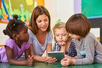 Kinder und Erzieherin beim Vorlesen aus einem Ebook