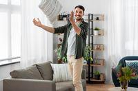 happy smiling man arranging sofa cushions at home