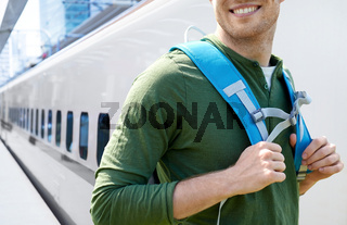 smiling man with backpack traveling over train