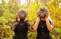 Two female friends holding scary green pumpkins in front of her face
