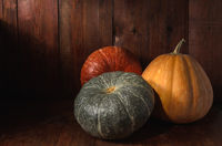 group of pumpkins on a dark wooden background in rustic style