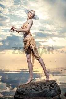 Young beautiful woman as swan posing on the beach at sunset