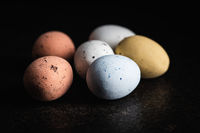 Colorful chocolate easter eggs. Sweet candy eggs on black table.