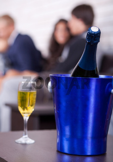 Champagne in focus, couples in background