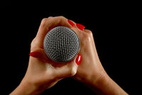 Woman hands with microphone isolated on black