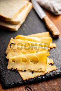 Sliced smoked hard cheese.