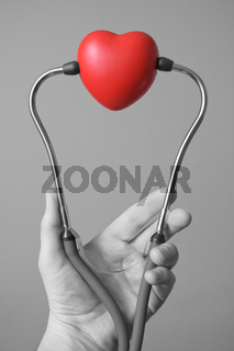 Man's hand holding a red heart and stethoscope
