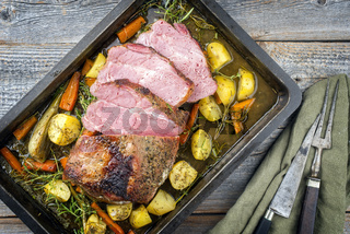 Traditional corned pot pork roast sliced and offered with potatoes