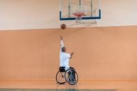 a photo of a war veteran playing basketball in a modern sports arena. The concept of sport for people with disabilities