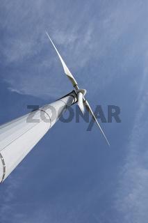 Drehende Windturbine vor blauem Himmel