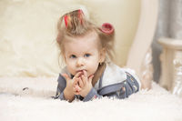A cute little girl in curlers lies on the bed and looks at the camera.