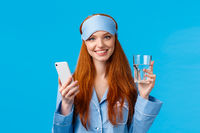 Waist-up portrait cheerful attractive glamour woman with red, ginger hair in sleep mask and pyjama, holding glass water and smartphone, smiling camera, standing blue background