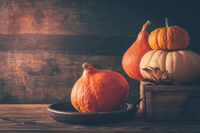 Happy thanksgiving - still life with different pumpkins and autumn leaves on wooden background