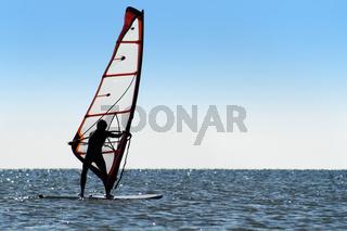 Silhouette of a windsurfer on the blue sea