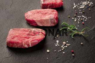 Raw beef steaks with salt, pepper and rosemary