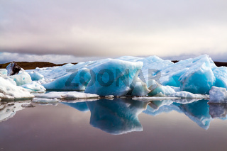 The icebergs reflected in the smooth water