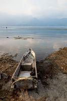 Local wooden fishermen canoe at the coast along lake Atitlan during sunset in Guatemala