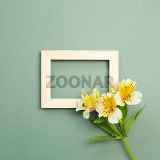 Wooden picture frame with yellow flower bouquet on green background. top view, copy space