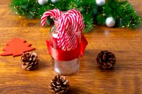 Composition of christmas decorations with candy canes, pine cones and garland on wooden background