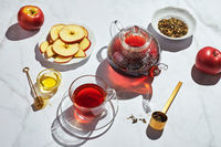 Fruit tea with apples and thyme and honey in glass teapot and cup on white background with hard shadows