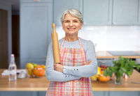 smiling senior woman in apron with rolling pin
