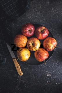 Fresh autumn apples on black table.