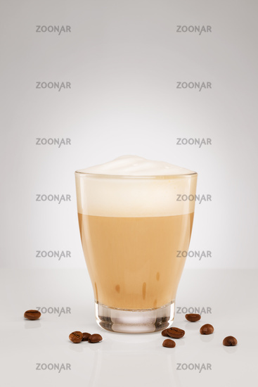 cappuccino in a small glass with coffee beans