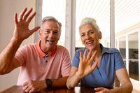 Happy caucasian senior couple having video call, waving to camera
