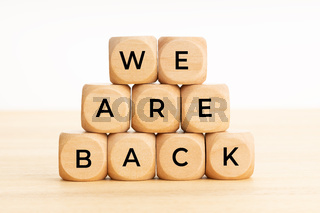 We are back concept. Words on wooden blocks on table. Copy space