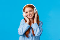 Technology, lifestyle and people concept. Cute redhead woman in pyjama, listen music in headphones, enjoy nice beats in earphones, good quality, new songs, standing blue background