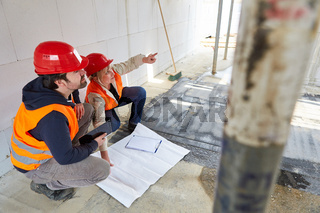 Architekten Team mit Grundriss auf der Baustelle