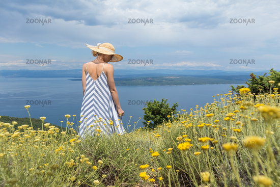 Rear view of young woman wearing striped summer dress and straw hat standing in super bloom of wildflowers, relaxing while enjoing beautiful view of Adriatic sea nature, Croatia