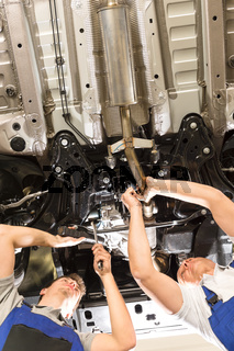 Caucasian repairmen working under automobile