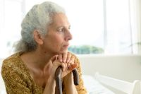 Profile of thoughtful caucasian senior woman holding rod and looking into distance