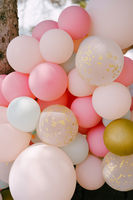 Close-up of many helium balloons in pastel colors.