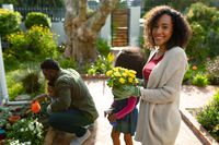 Happy african american mother holding flowers, gardening with children and husband