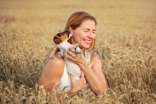 Young woman in wheat field holding Jack Russell terrier puppy, that is licking her ear.